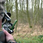 Man holding rifle taking aim at Muntjac