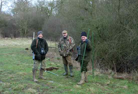 three men holding rifles in woodland clearing