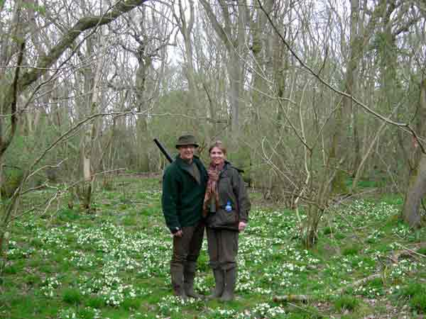 Two people standing in woodland in springtime